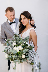 Portrait of a beautiful couple in love on your wedding day. Walking near the house with white walls and greenery. Amazing kisses and embraces of the bride and groom with a bouquet