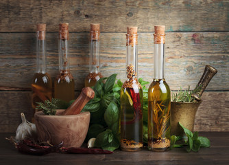Olive oil with different spices and herbs on a wooden table.