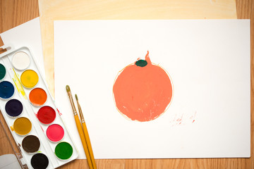 red apple, orange orange on a white sheet of colored paperchildren's drawing with colored pencils and watercolors
