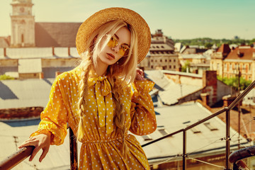 Outdoor portrait of young beautiful girl wearing trendy yellow color sunglasses, straw boater hat, polka dot dress posing in street of european city. Summer fashion concept. Copy. empty space