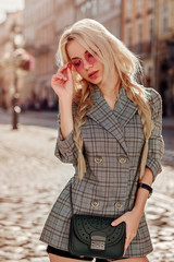 Outdoor portrait of beautiful fashionable woman wearing pink sunglasses, double-breasted Prince of Wales-print blazer, with crossbody bag, posing in street of european city. Female fashion concept