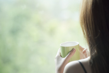 Cropped image of sexy woman holding a cup of  coffee standing near the window