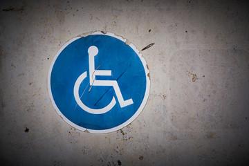 Symbol für einen Behindertenparkplatz an der Wand eines Parkhauses