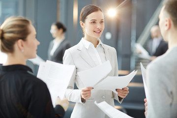 Young confident businesswoman with documents having talk with one of colleagues at working meeting