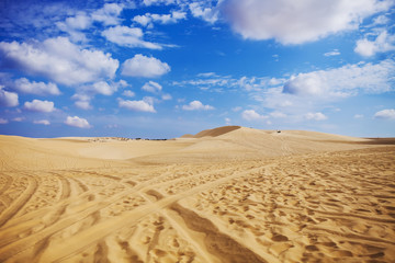 Sand dunes near Mui Ne. Group of off roads on top of dunes in the background. Sunny day with blue sky and clouds