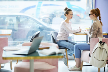 Two friendly girls in casualwear sitting in college cafe after lessons and discussing topics of their thesis