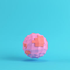 Pink abstract low poly planet on bright blue background in pastel colors