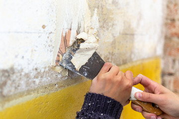 Junge Frau mit Spachtel in der Hand renoviert