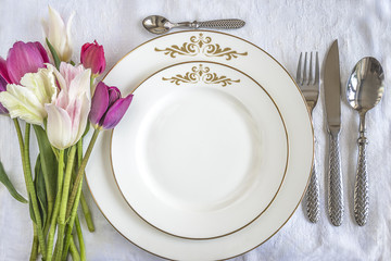Festive table setting: beautiful cutlerly, white plates and bouquet of multicolored tulips on white linen tablecloth top view