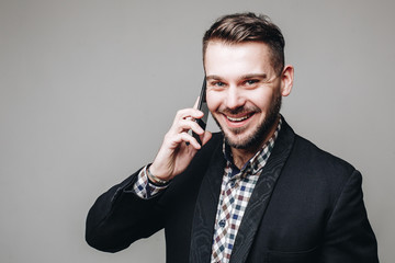 Close up portrait of beautiful handsome business man in suit smiling while talking on the cell phone isolated on grey background. Indoors, studio