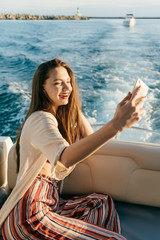 an attractive funny girl swims to the islands on vacation on her yacht, makes selfie on her smartphone