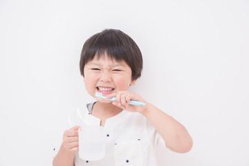 歯ブラシとコップを持つ男の子