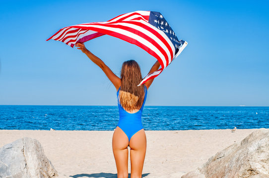 Beautiful cheerful woman holding an American flag on the beach.
