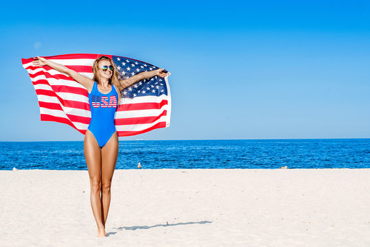 Beautiful patriotic cheerful woman holding an American flag on the beach.