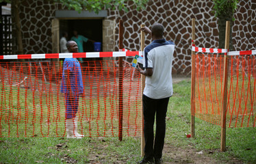 A resident speaks to a medical worker through a cordon ribbon, near the isolation facility prepared to receive suspected Ebola cases, at the Mbandaka General Hospital, in Mbandaka