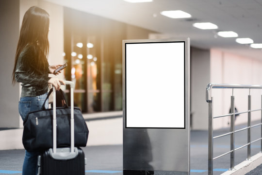 traveller woman looking blank advertising billboard at airport.