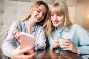 Young woman shows photos to her girlfriend in cafe