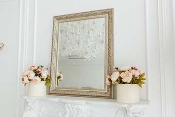 square vintage mirror frame on the livingroom wall over fireplace with photo frame, and flowers bouquet