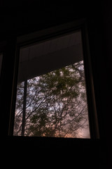Sunset interior window view with dark negatives space and muted colors through the window
