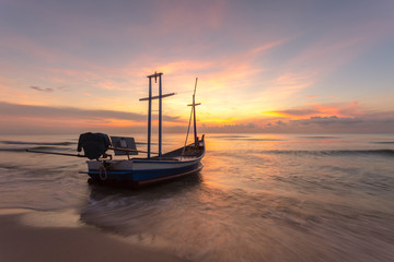 Fishing boat on the beach near sunset.