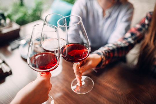 Girlfriends clink glasses with red wine