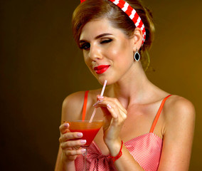 Retro woman with music vinyl record. Pin up girl drink martini cocktail. Girl pin-up retro style wearing red dress on dark background. Female flirtatiously winks.