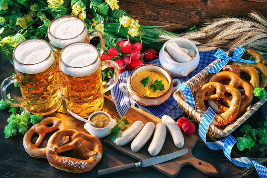 Bavarian sausages with pretzels, sweet mustard and beer mugs on rustic wooden table