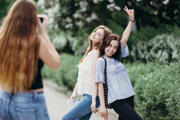 Photographing, hobby, leisure, traveling, friendship. Woman taking picture of her friends using camera