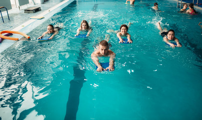 Male trainer swims with female aqua aerobics group
