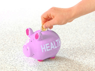 """putting a coin in a piggy bank with the word """"health"""" as an inspiration to invest in health"""