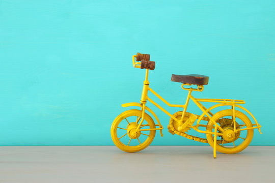 Vintage metal yellow bicycle toy over wooden table.