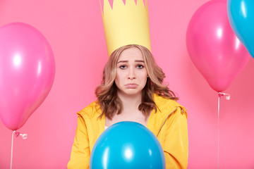 Disappointed young woman in party hat surrounded by colorful balloons, isolated over pastel pink background. Sad Birthday Party concept.
