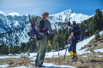 Hikers with trekking poles stand in the snowy mountains at the foot of the peak. Concept of travel and achieve the goal