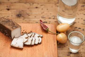 Pieces of salted lard, garlic, black pepper and onion on cutting board on wooden table. Top view