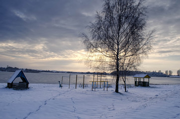 a house on the shore of a lake in winter at sunset