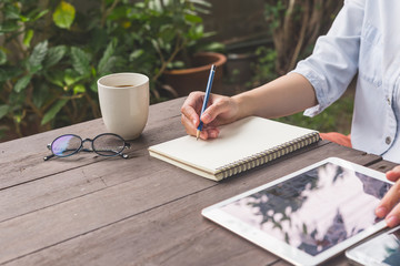 Hand woman writing notebook on wood table with cup coffee and tablet.