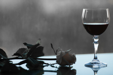 Glass of red wine on a gloomy background. unhappy love. Bed evening.