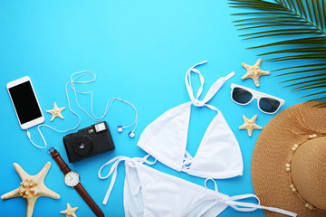 White swimsuit with starfishes and accessories on blue background
