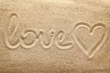 Inscription Love and heart drawn on beach sand