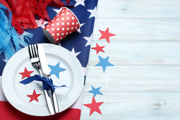 American flag with plate and kitchen utensils on wooden table