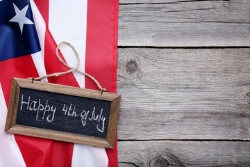 American flag and wooden frame with inscription Happy Independence Day