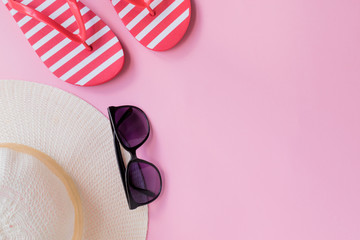 Summer hat, flip flops and sunglasses on a pink background