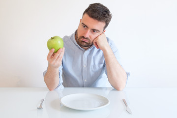 Sad and frustrated man on diet having only fruit for meal