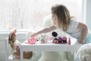 A little girl having a pretend tea party.