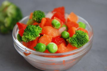 Frozen Colorful Vegan Healthy Vegetables. Brocolli, Carrots, Peas, Pepper. vertical Image. Gray Background.