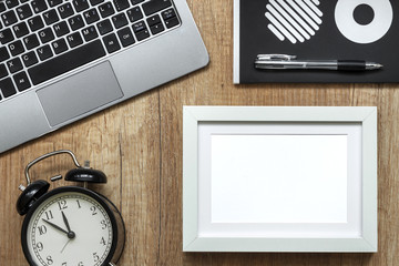 A wooden desk with a laptop, a black watch, a notebook in circles and a white empty frame
