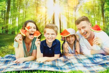 Enspannte Familie mit Kindern im Park auf der Decke
