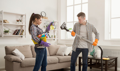 Young couple cleaning home, playing with mop