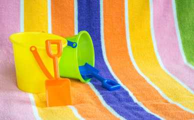 2 child's plastic sand pails and shovels on a colorful striped beach towel with copy space