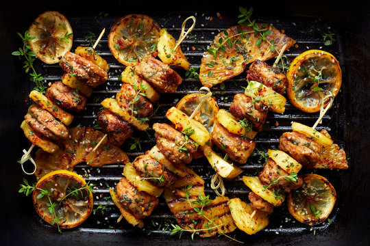Grilled skewers with chicken meat and pineapple with herbs on a grill plate. Fruit and meat skewers, top view